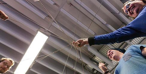 Professorin und Studierende halten die Fäden eines Fadennetzes