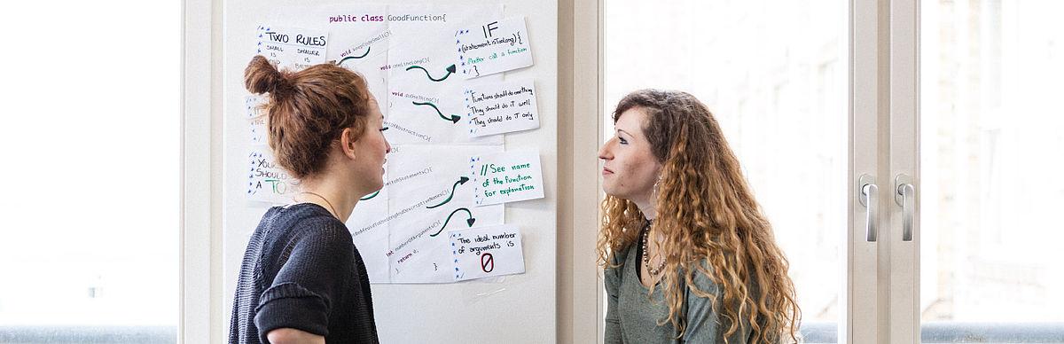 Zwei Studentinnen vor einer Minmap an der Wand