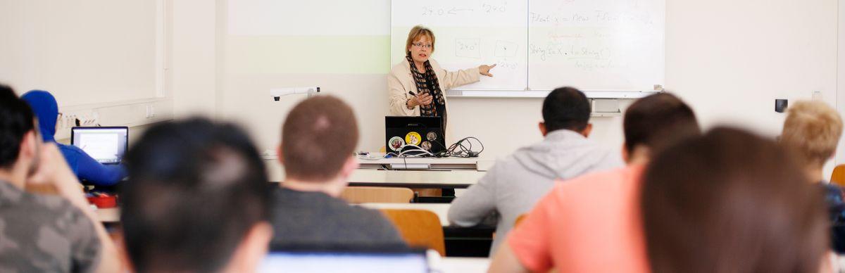 Professorin erklärt im Unterricht etwas an der Tafel